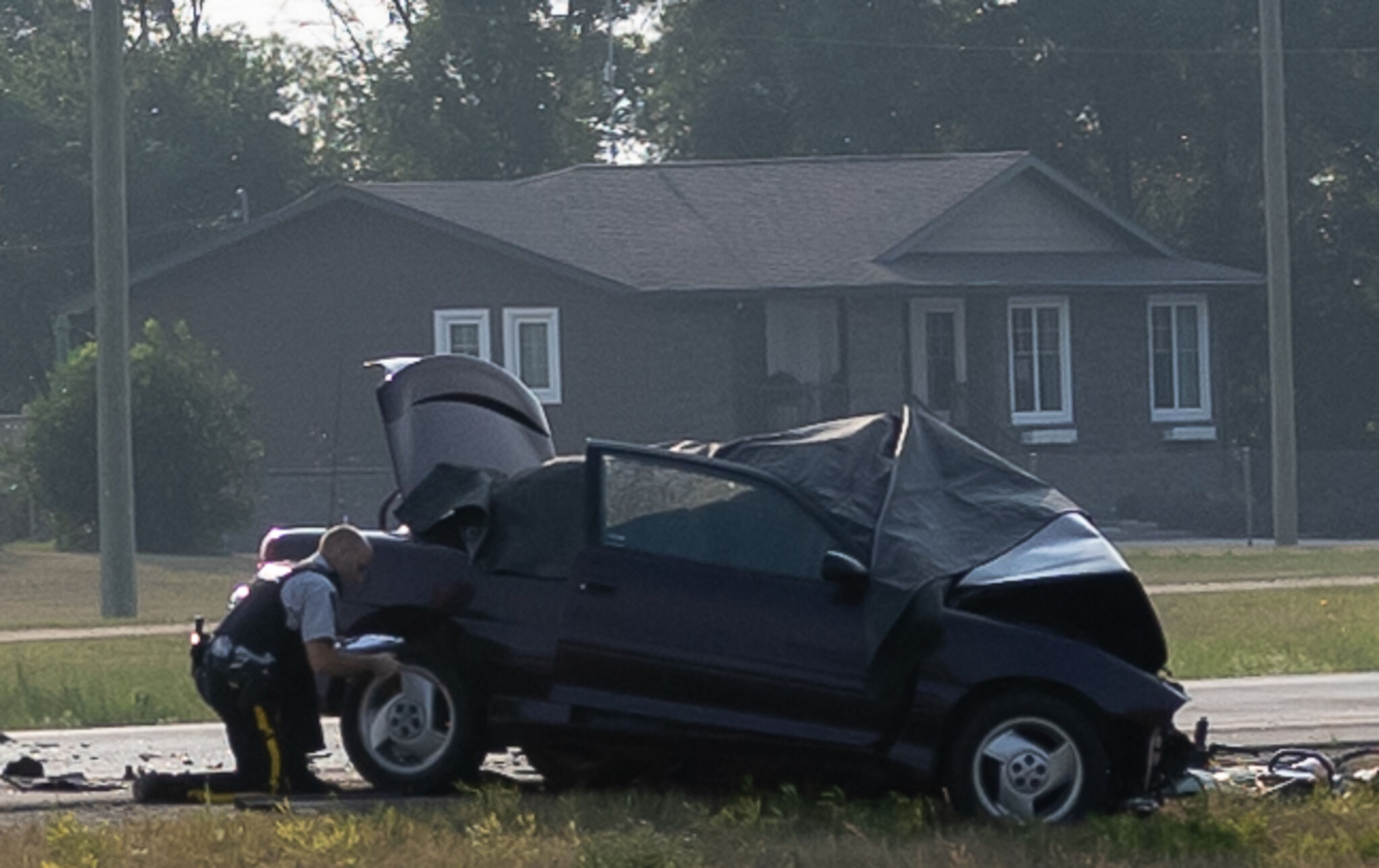 An RCMP officer examines one of the vehicles involved.
