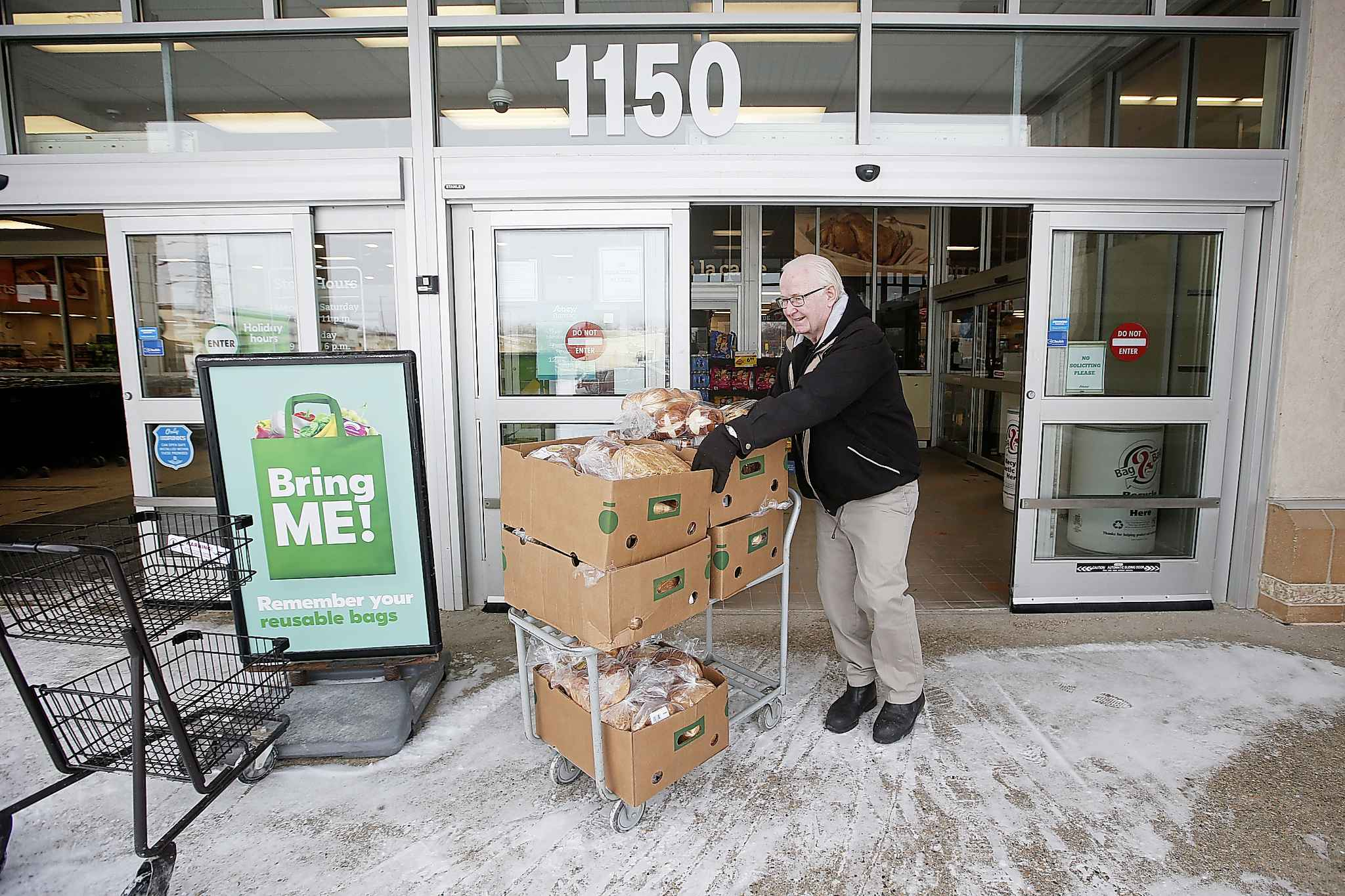 Ted Martens gathers food in the early morning at a local grocery store for volunteers to feed and support about 100 people at the Love Lives Here drop-in.