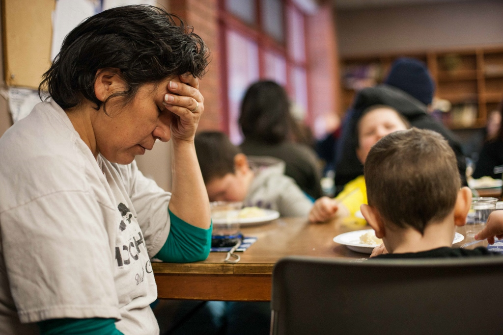 Diana Chartrand takes a moment of calm to pray before sharing a Christmas Day meal put on by the Shaarey Zadek synagogue for 150 needy people at the West Broadway Community Ministry. (Jesse Winter / Winnipeg Free Press)