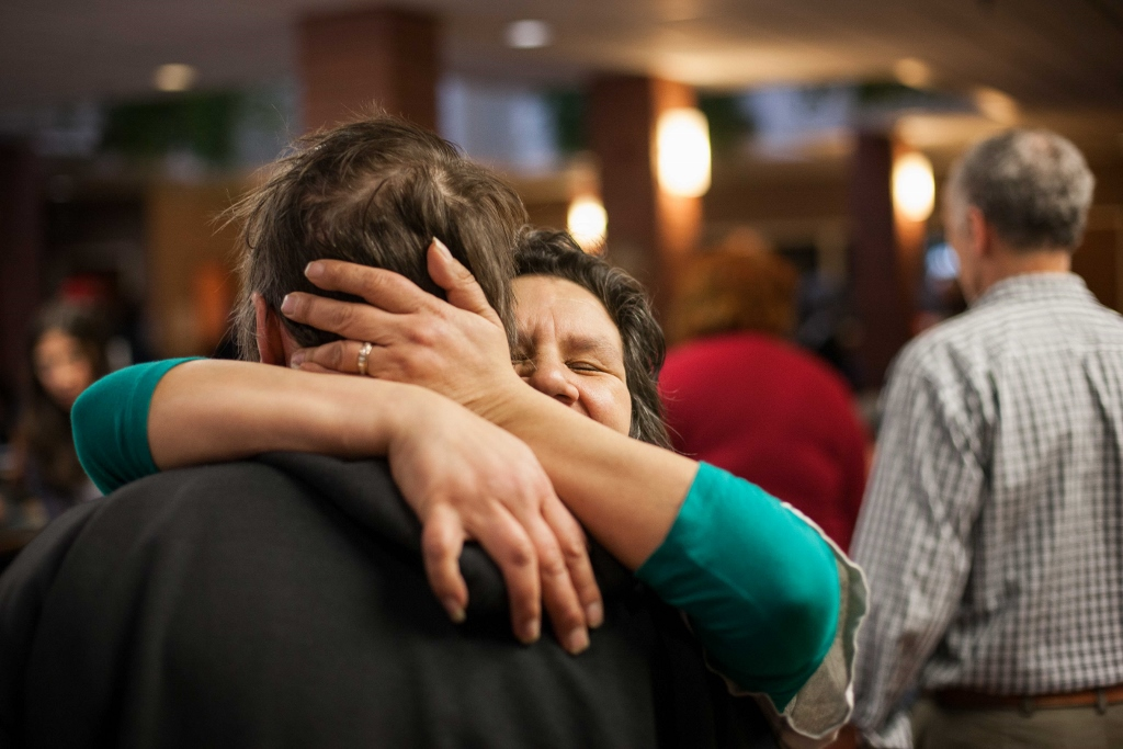 Diana Chartrand embraces her partner Bill Trnka before a Christmas Day meal at the West Broadway Community Ministry. (Jesse Winter / Winnipeg Free Press)