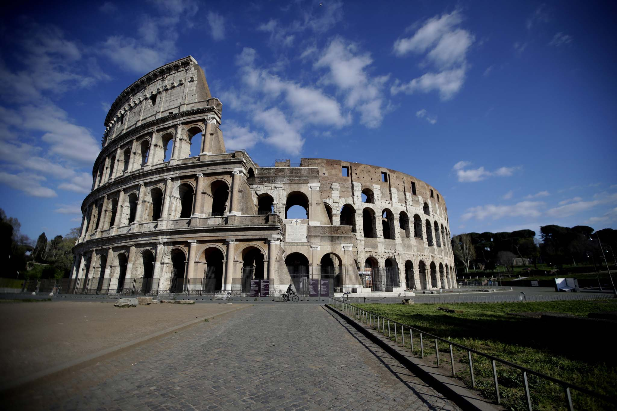 A man pedals in front of an empty area outside Rome's ancient Colosseum.