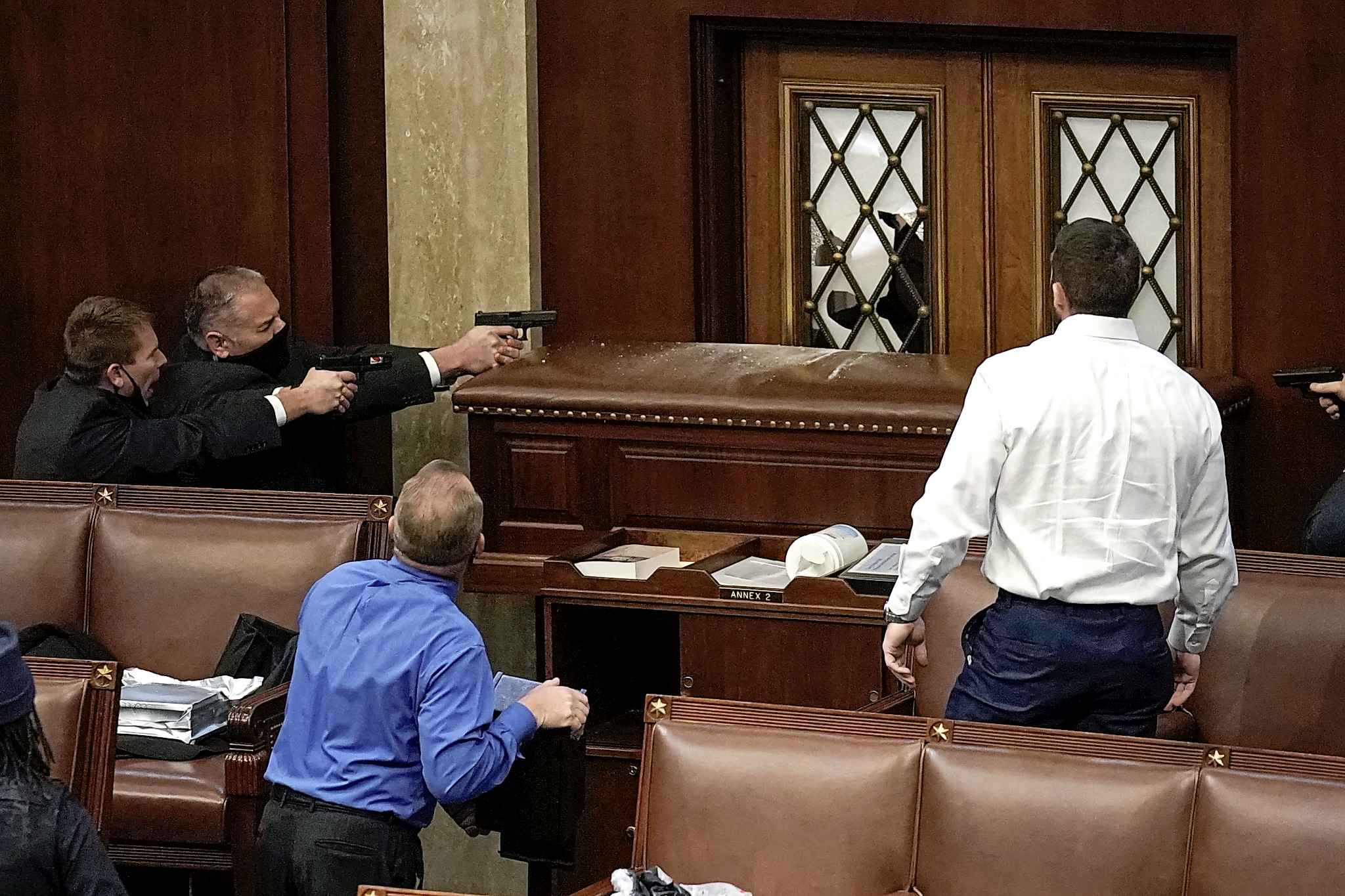 Police with guns drawn watch as protesters try to break into the House Chamber at the U.S. Capitol on Wednesday, Jan. 6, 2021, in Washington. (AP Photo/J. Scott Applewhite)