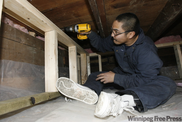 Chris Courchene screws in a frame to insulate a basement in an Aberdeen Avenue home in December 2008.