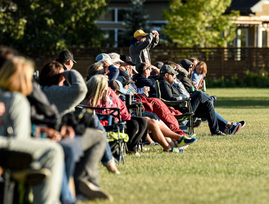 Spectators keep their distance as they watch a U14 soccer game Monday evening.