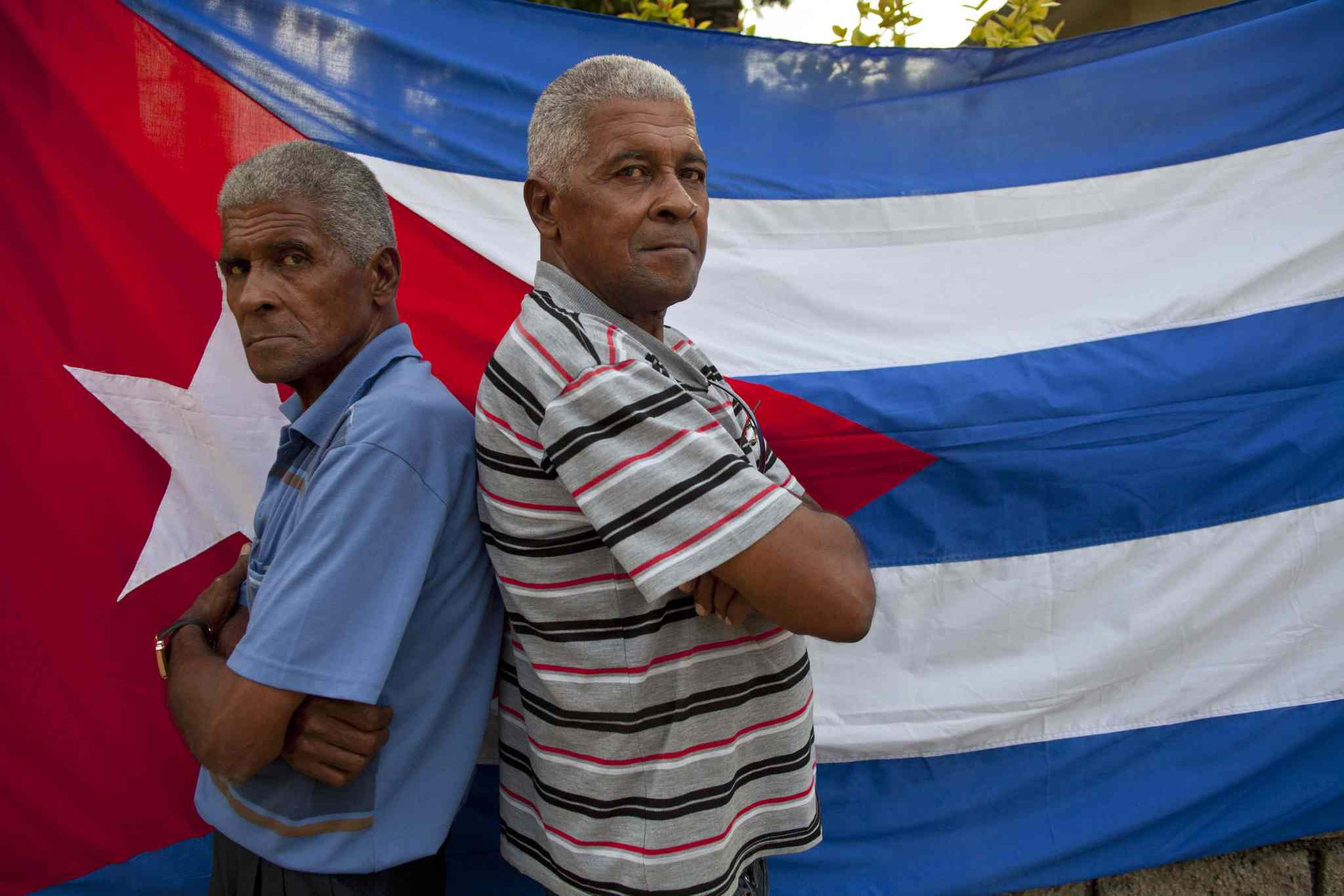 Twins Orlando Gonzalez, left, and Roberto Gonzalez pose for a portrait in front a Cuban flag along their street in Havana, Cuba.