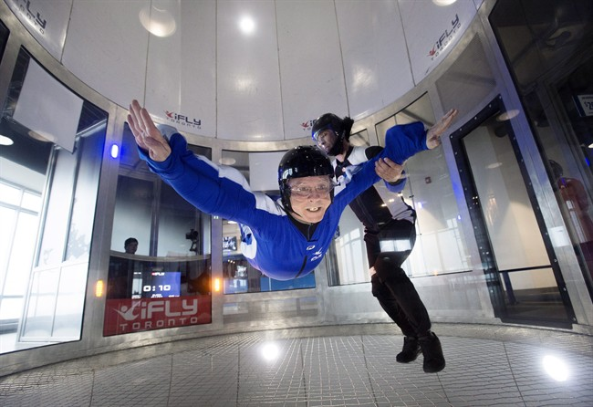Jeff Finkler, left, is guided by an instructor while trying indoor skydiving at iFly Toronto in Oakville, Ont. on Wednesday, March 25, 2015. THE CANADIAN PRESS/Darren Calabrese