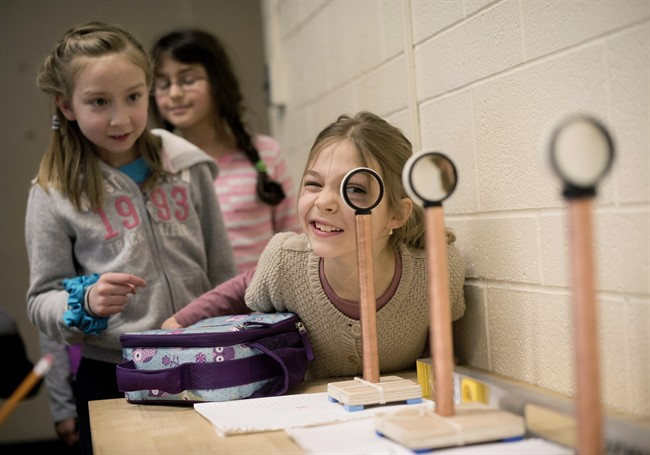 Catherine Makarytchev, 8, right, takes her turn looking through magnifying lenses while performing experiments at a junior science program at the University of Toronto in Toronto on Saturday, February 28, 2015. THE CANADIAN PRESS/Darren Calabrese