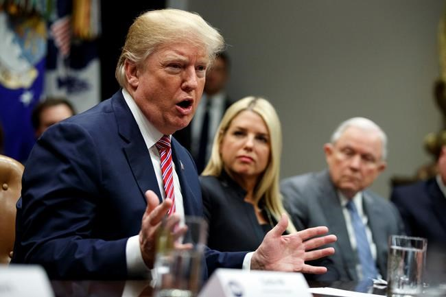Florida Attorney General Pam Bondi, center, and Attorney General Jeff Sessions, right, watch as President Donald Trump speaks during a meeting with state and local officials to discuss school safety, in the Roosevelt Room of the White House, Thursday, Feb. 22, 2018, in Washington. (AP Photo/Evan Vucci)