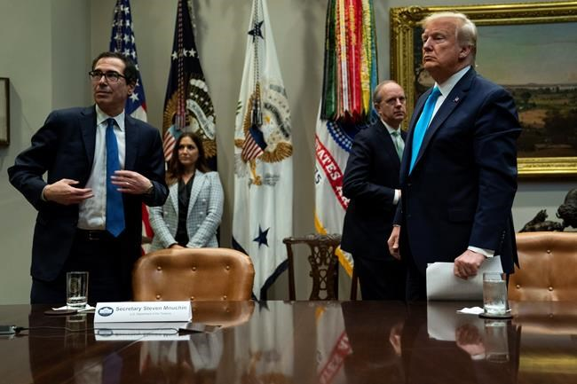 Treasury Secretary Steven Mnuchin and President Donald Trump listen to a question during a conference call with banks on efforts to help small businesses during the coronavirus pandemic, at the White House, Tuesday, April 7, 2020, in Washington. (AP Photo/Evan Vucci)