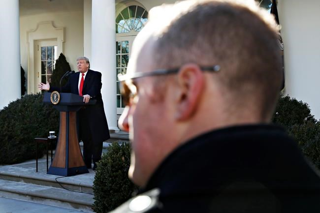 With a Secret Service agent watching in the foreground, President Donald Trump announces a deal to temporarily reopen the government, Friday, Jan. 25, 2019, in the Rose Garden of the White House in Washington. (AP Photo/Jacquelyn Martin)
