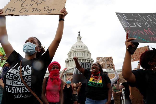 Dominique Bryant, 23, wearing the Black and Proud T-shirt, joins demonstrators as they protest the death of George Floyd, Wednesday, June 3, 2020, outside the U.S. Capitol in Washington. Floyd died after being restrained by Minneapolis police officers. (AP Photo/Jacquelyn Martin)