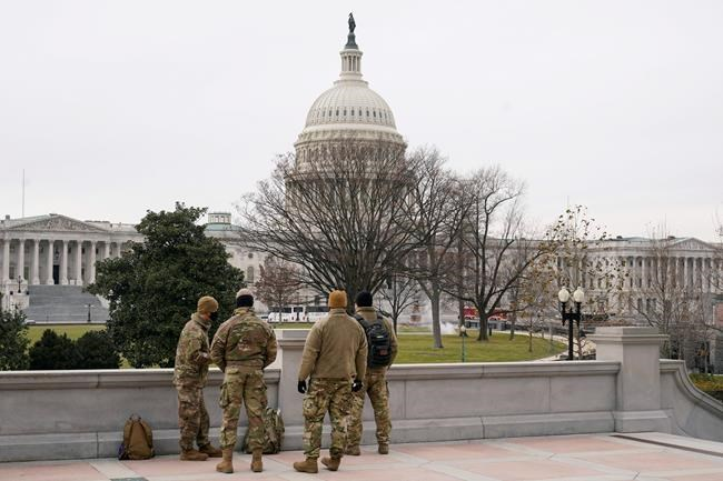 With the U.S. Capitol Building in view, members of the military stand on the steps of the Library of Congress's Thomas Jefferson Building in Washington. (Patrick Semansky / The Associated Press files)