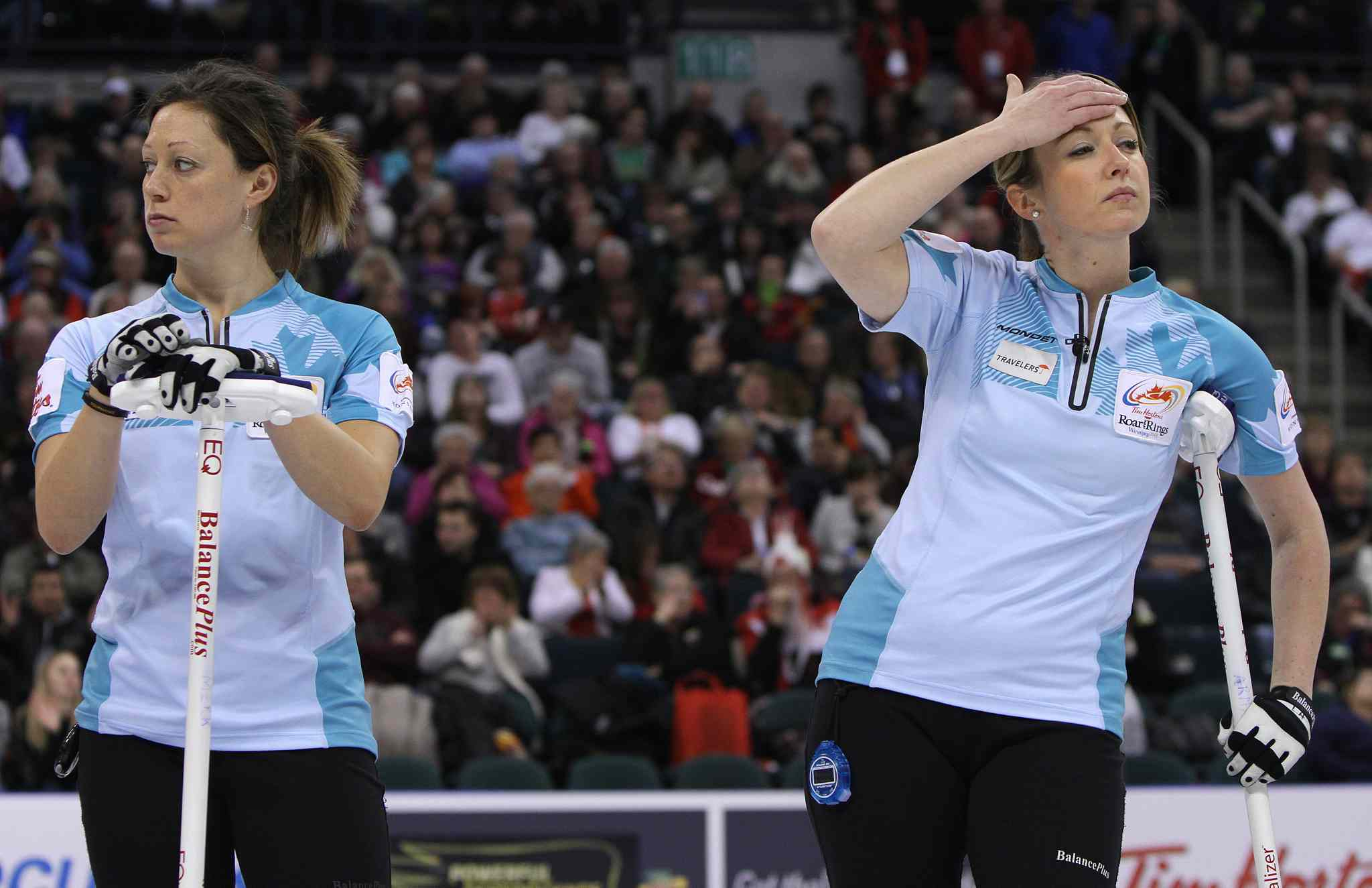 Sherry Middaugh's second Lee Merklinger (left) and lead Leigh Armstrong react to a shot.