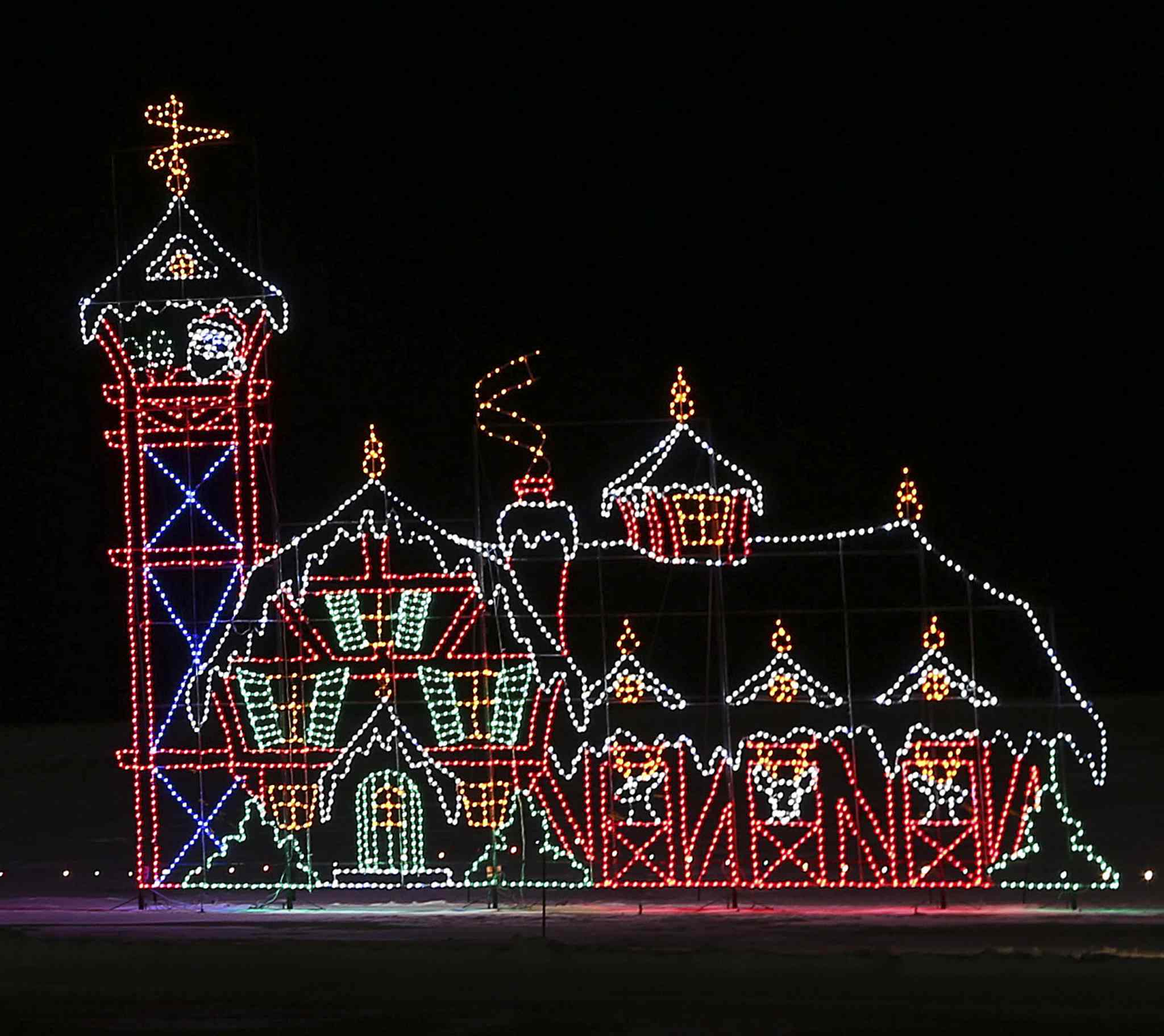 An illuminated Santa Claus waves to visitors from the tower of a building made of lights.