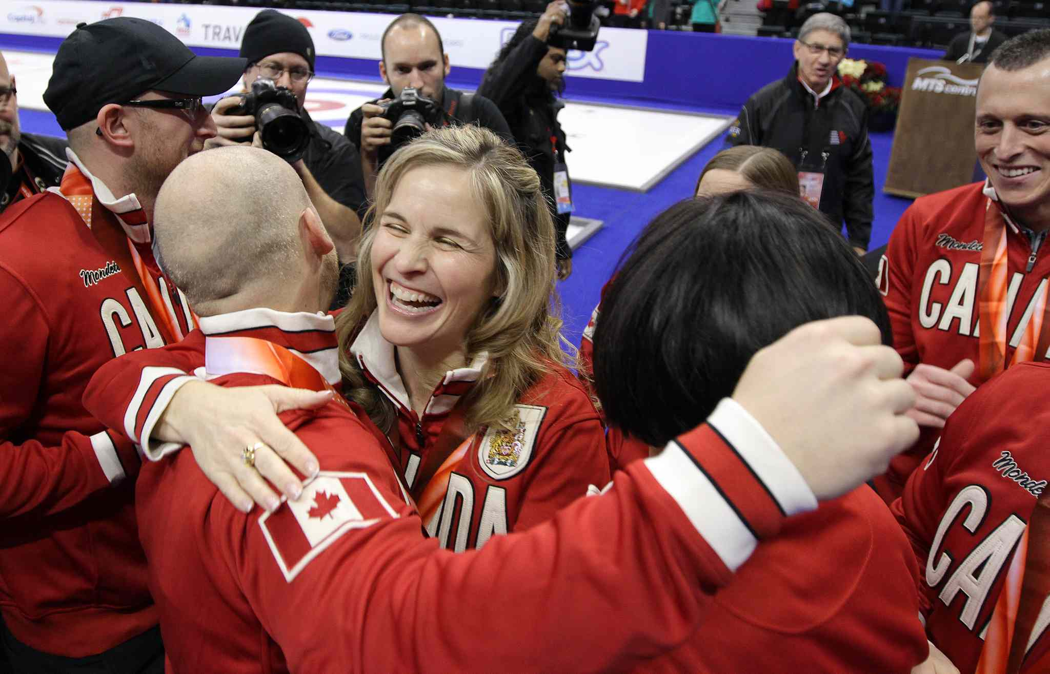 Skip Jennifer Jones (centre) and Ryan Fry hug after the men's team was presented with their Team Canada jackets and Roar of the Rings medals.