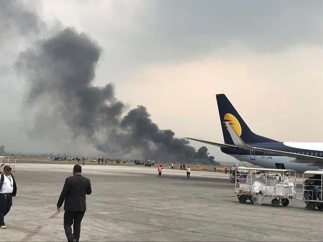 Smoke rises after a passenger plane from Bangladesh crashed at the airport in Kathmandu, Nepal, Monday, March 12, 2018. A passenger plane carrying 71 people from Bangladesh crashed and burst into flames as it landed Monday in Kathmandu, Nepal's capital, killing dozens of people with others rushed to area hospitals, officials said.(Bishnu Sapkota via AP)