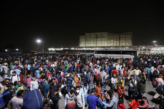 Hundreds of migrant workers wait at a bus station to leave for their villages, in New Delhi, India, Monday, April 19, 2021. New Delhi has imposed a week-long lockdown to prevent the collapse of the Indian capital's health system amid an explosive surge in coronavirus cases. Authorities said Monday that hospitals have been pushed to their limit. India now has reported more than 15 million coronavirus infections, a total second only to the United States. (AP Photo)