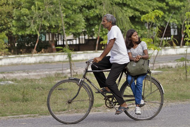 Tej Bahadur Verma, 50, takes his daughter Sushma Verma home from her school in Lucknow, India, Monday, Sept. 16, 2013. Verma, from a poor family in north India, enrolled in a master's degree in microbiology, after her father sold his land to pay for some of his daughter's tuition in the hope of catapulting her into India's growing middle class. Verma finished high school at 7 and earned an undergraduate degree at age 13 - milestones she said were possible only with the sacrifices and encouragement of her uneducated and impoverished parents. (AP Photo/Rajesh Kumar Singh)