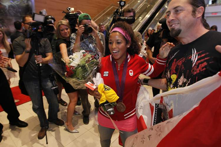 Soccer Olympian and bronze medallist Desiree Scott is welcomed home by her brother, Christopher Hawkins, and fans at Richardson International Airport on Monday.