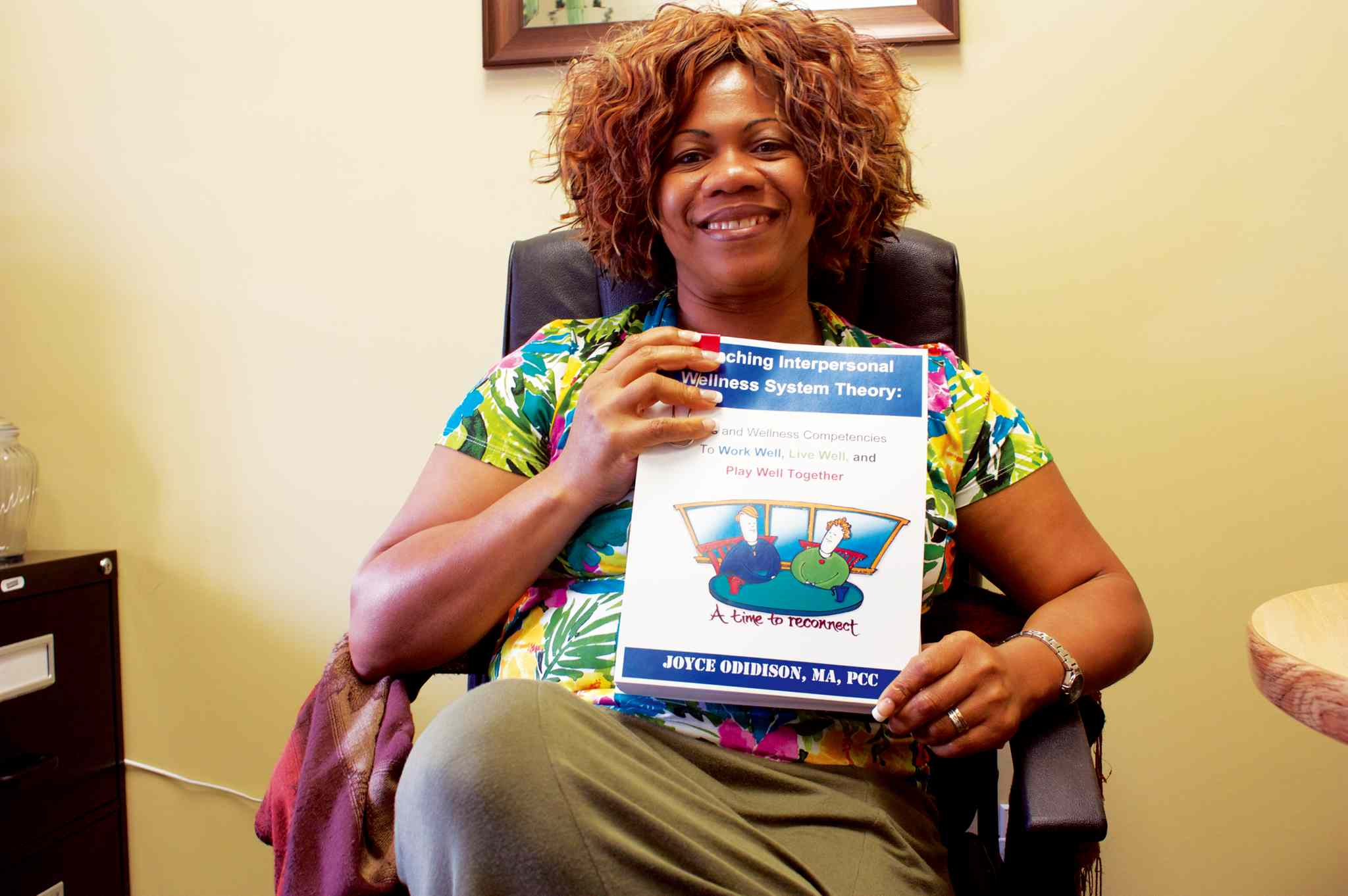 Interpersonal Wellness Services Inc. founder Joyce Odidison is shown with her fifth book, Coaching Interpersonal Wellness System Theory.