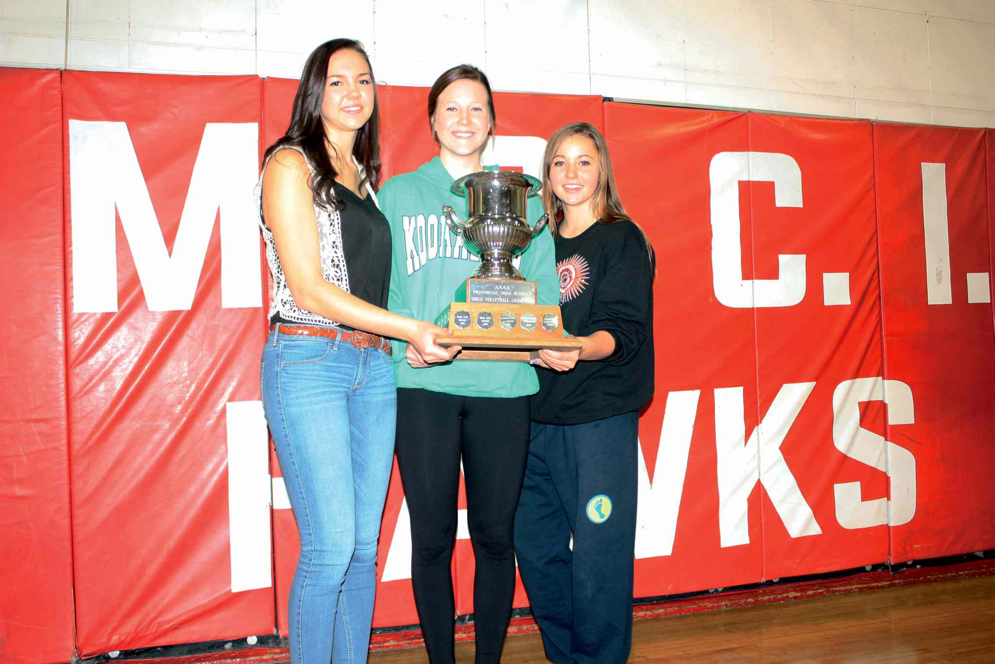 Mennonite Brethren Collegiate Institute Hawks varsity girls' volleyball players Kalena Schulz, Shayna Staerk, and Maiya Westwood are shown with the fruits of victory after capturing the Boston Pizza AAAA Volleyball Championships on Dec. 2.