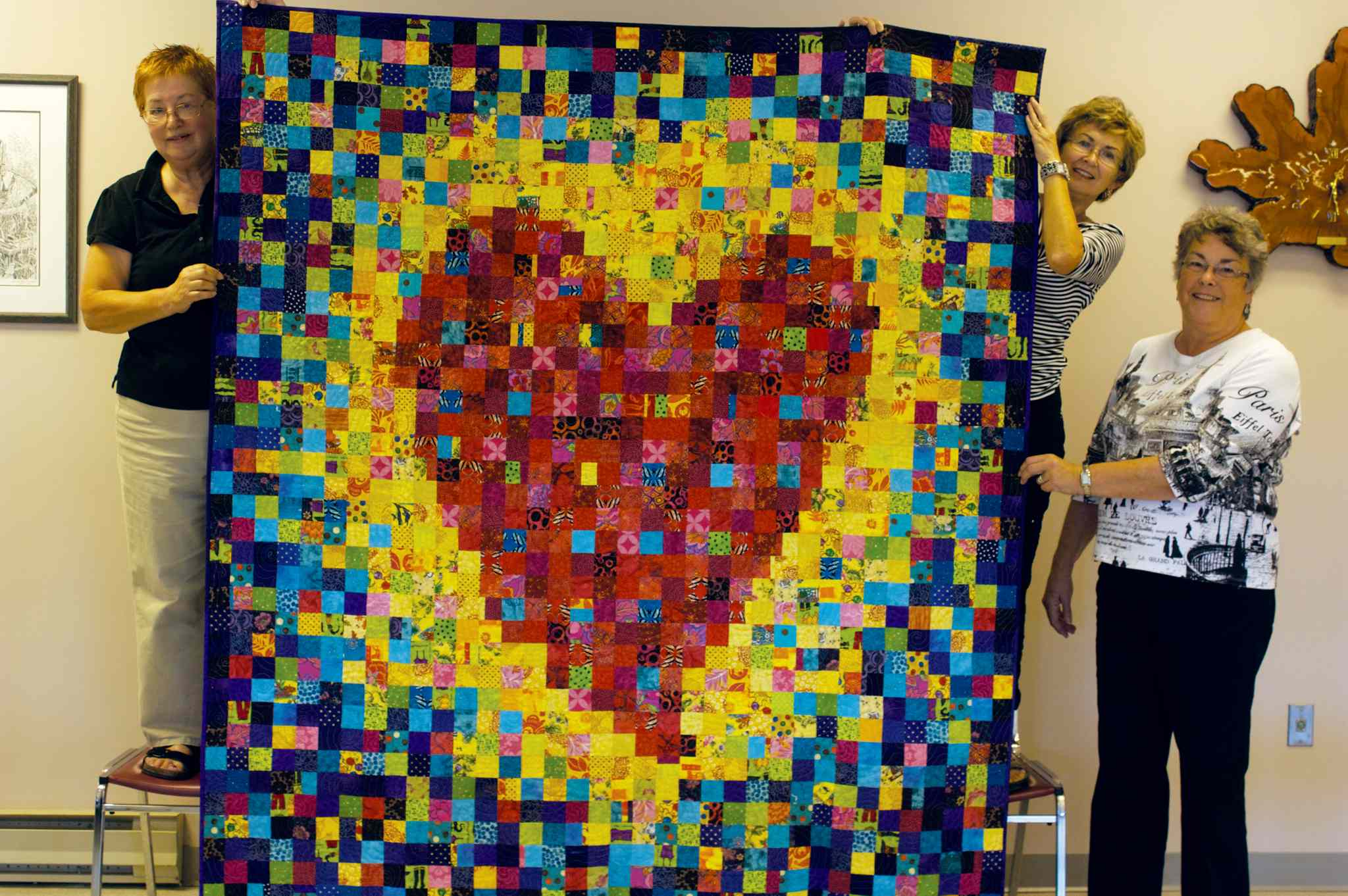 Fran Howard (left) holds up one of her quilts with help from Material Girls club members Rita Toews and Leone Newton.