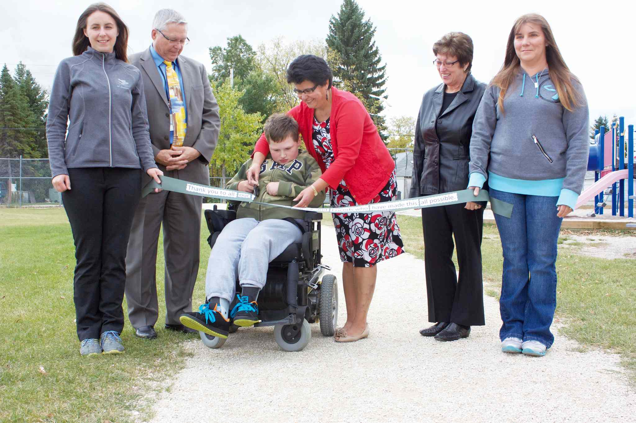 Prince Edward Community School principal Linda Mauthe helps Grade 6 student Quinton Ullman (centre) cut the ribbon for the school's revamped walking path on Oct. 3. They are flanked by advisory council president Marni McCluskey (far left), vice-president Jacquie Meilleur (far right), assistant superintendent Keith Morrison (second from left), and Ward 4 trustee Eva Prysizney (second from right).
