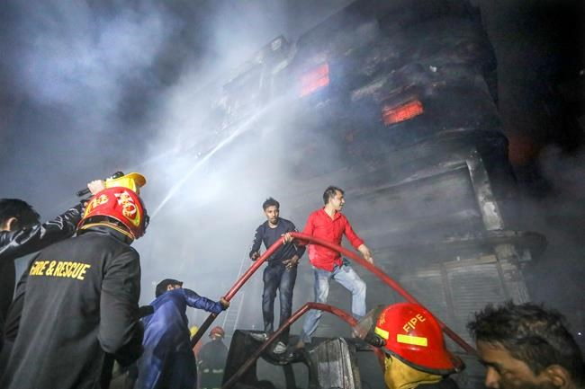 locals and firefighters douse flames of a smoldering fire in a building in Dhaka, Bangladesh, Thursday, Feb. 21, 2019. The devastating fire raced through buildings in an old part of Bangladesh's capital and killed scores of people. (AP Photo)