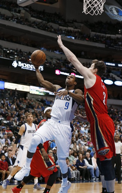 Dallas Mavericks guard Rajon Rondo (9) takes a shot as New Orleans Pelicans center Omer Asik (3) defends during the first half of an NBA basketball game Monday, March 2, 2015, in Dallas. (AP Photo/Sharon Ellman)