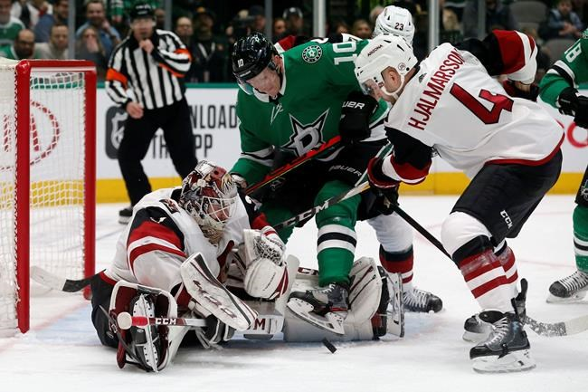 Arizona Coyotes goaltender Adin Hill (31) defends a shot in front of Dallas Stars right wing Corey Perry (10) and Coyotes defenseman Niklas Hjalmarsson (4) during the first period of an NHL hockey game in Dallas, Wednesday, Feb. 19, 2019. (AP Photo/Michael Ainsworth)