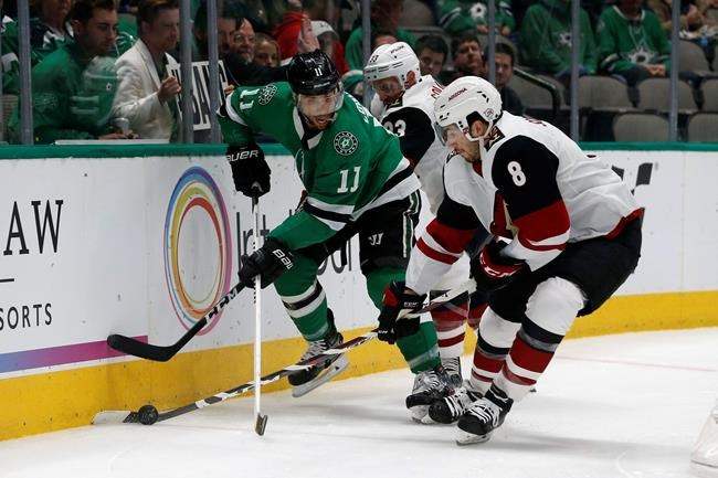 Dallas Stars center Andrew Cogliano (11) and Arizona Coyotes defenseman Alex Goligoski (33) and center Nick Schmaltz (8) work along the boards during the first period of an NHL hockey game in Dallas, Wednesday, Feb. 19, 2019. (AP Photo/Michael Ainsworth)