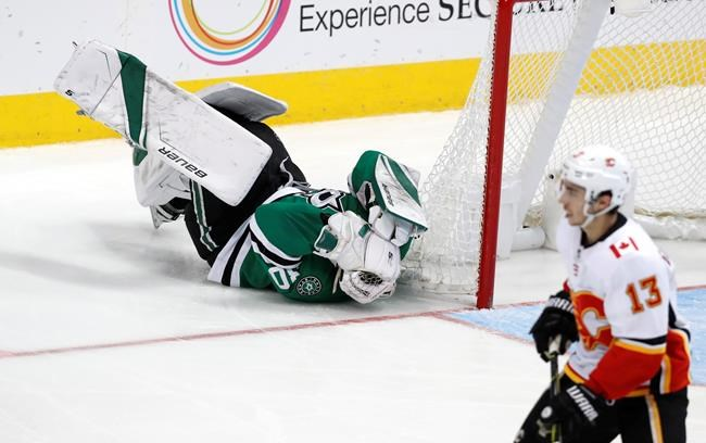 Dallas Stars goaltender Ben Bishop (30) lays on the ice after getting hit as Calgary Flames left wing Johnny Gaudreau (13) skates by during the second period of an NHL hockey game in Dallas, Tuesday, Dec. 18, 2018. (AP Photo/LM Otero)