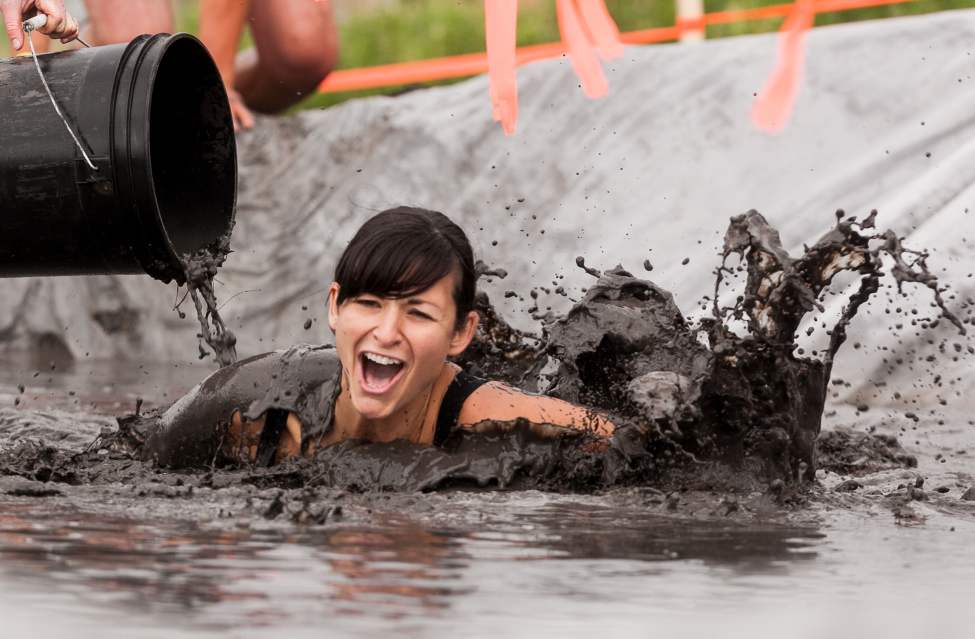 Tricia Garton gets down and dirty near the finish line at the Dirty Donkey Mud Run on Saturday morning. (Melissa Tait / Winnipeg Free Press)