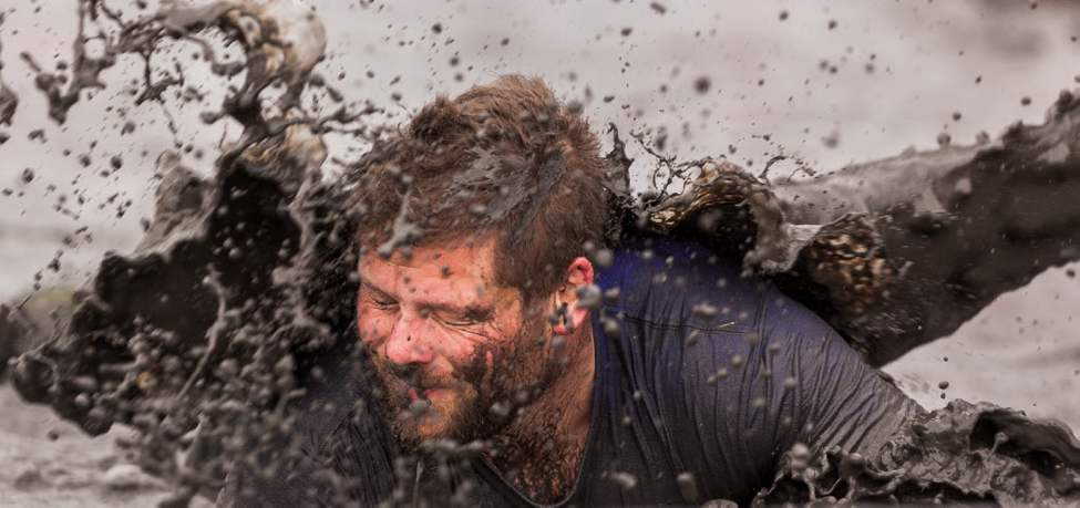 Jason Penner takes a face full of muddy water near the finish line of the Dirty Donkey Mud Run Saturday morning.  (Melissa Tait / Winnipeg Free Press)