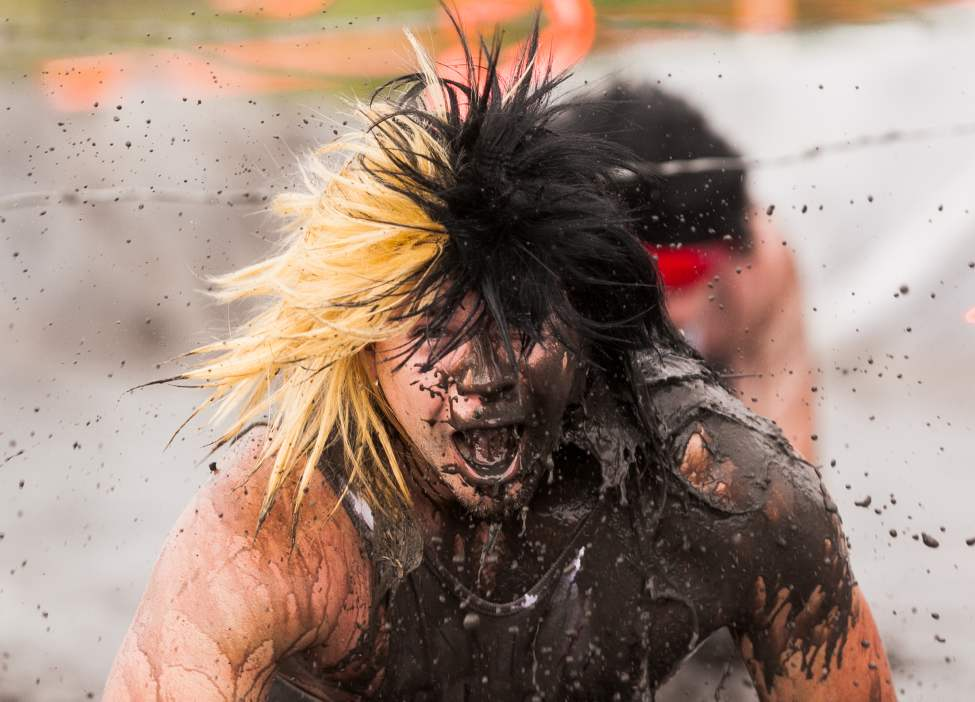 Mike Sadlowski reacts to a splash of mud water near the finish line of the Dirty Donkey Mud Run Saturday morning.  (Melissa Tait / Winnipeg Free Press)