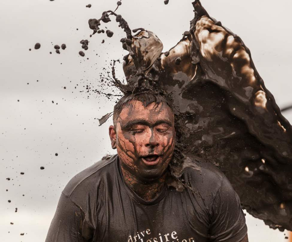 Mike Morfoot takes a splash of mud near the finish line of the Dirty Donkey Mud Run Saturday morning.  (Melissa Tait / Winnipeg Free Press)