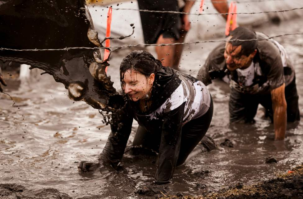 Laura Gallant braces for a splash of muddy water near the finish line of the Dirty Donkey Mud Run on Saturday morning.