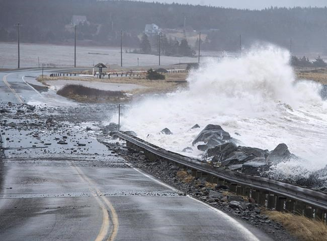 Waves pound the shore on a closed section of Highway 207 in Lawrencetown, N.S. on Friday, Jan. 5, 2018. A new analysis of flood risk suggests the yearly bills from overflowing rivers and rising seas could nearly triple by 2030, if Canada doesn't do more to improve flood protection. THE CANADIAN PRESS/Andrew Vaughan