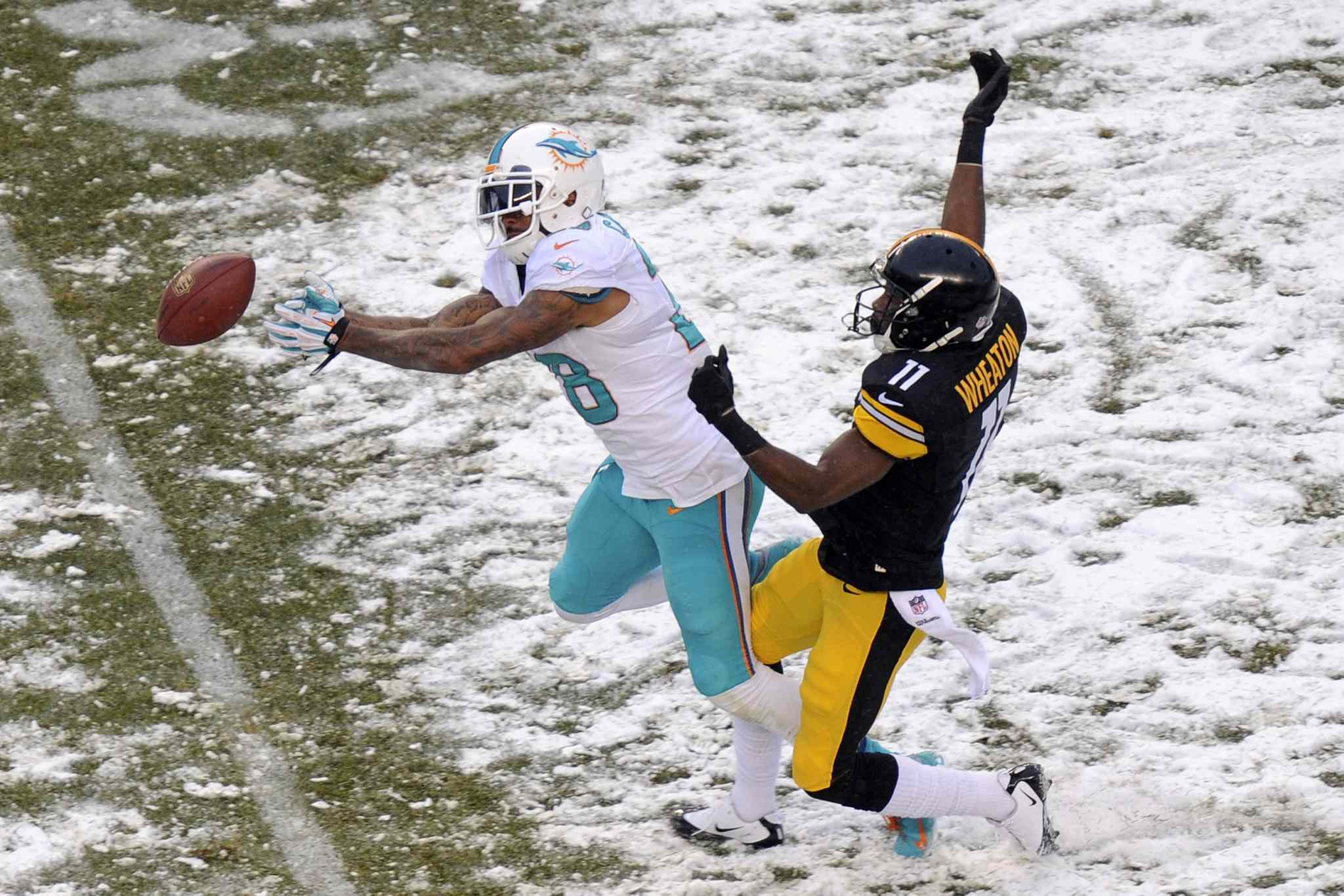 Miami Dolphins cornerback Nolan Carroll (left) can't come up with the interception of a pass intended for Pittsburgh Steelers wide receiver Markus Wheaton during the second half of an NFL football game in Pittsburgh on Sunday.