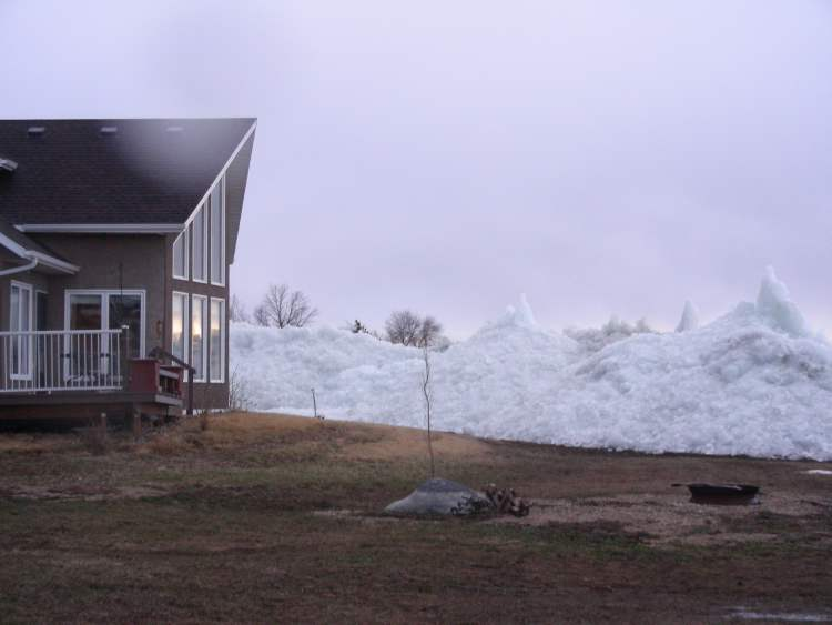 Piles of ice sit next to a building in the Dauphin Lake region. This building appears to have avoided the brunt of the damage.