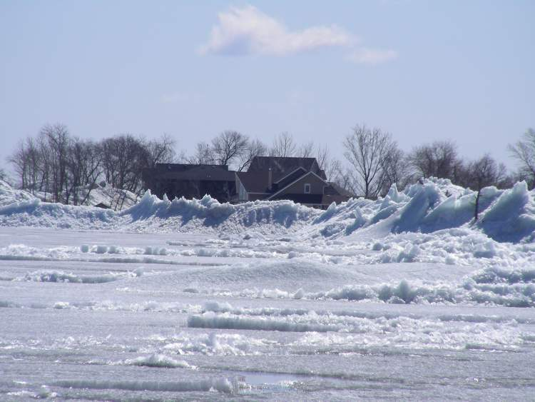 A field of ice is seen in front of a home in the Dauphin Lake region. (730 CKDM)