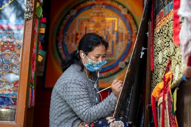 A woman wearing a mask to protect herself from the coronavirus paints a thangka, a traditional Tibetan Buddhist painting in Dharmsala, India, Tuesday, Sept. 15, 2020. (AP Photo/Ashwini Bhatia)