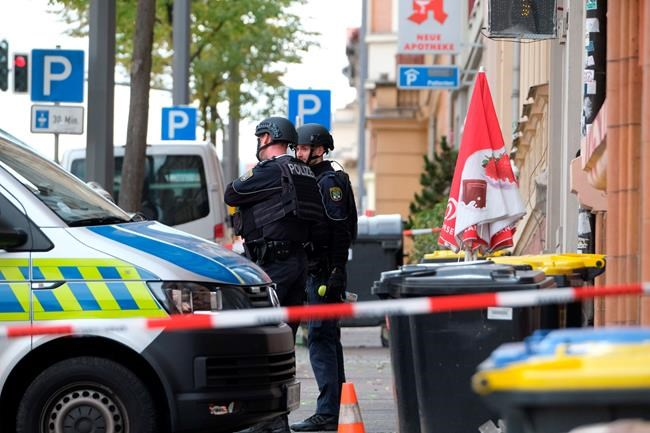 Police officers are seen at a crime scene in Halle, Germany, Wednesday, Oct. 9, 2019. A gunman fired several shots on Wednesday in the German city of Halle. Police say a person has been arrested after a shooting that left two people dead. (Sebastian Willnow/dpa via AP)