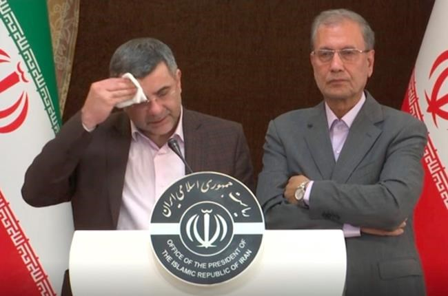 In this Monday Feb. 24, 2020 image made from video the head of Iran's counter-coronavirus task force, Iraj Harirchi, left, wipes his face during a press briefing with government spokesman Ali Rabiei, in Tehran, Iran. Harirchi, has tested positive for the virus himself, authorities announced Tuesday, amid concerns the outbreak may be far wider than officially acknowledged. The announcement regarding Harirchi came after the news conference seeking to minimize the danger posed by the outbreak. (APTN via AP)