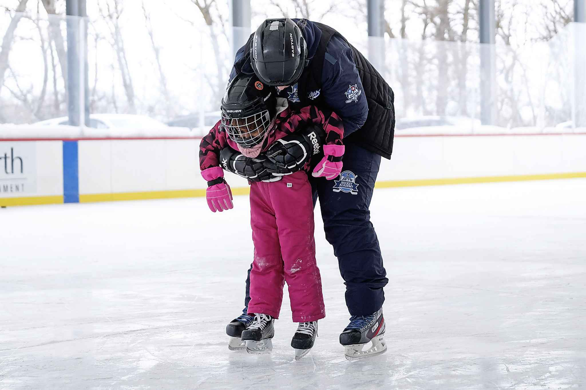 Letesus Takeia is helped to her feet during the Welcome to Winnipeg skating event.  (Daniel Crump / Winnipeg Free Press)</p>
