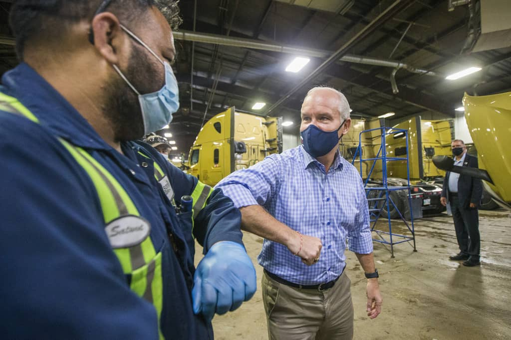 Conservative leader Erin O'Toole elbow-bumps mechanics after making an announcement at Bison Transport in Winnipeg on Friday.