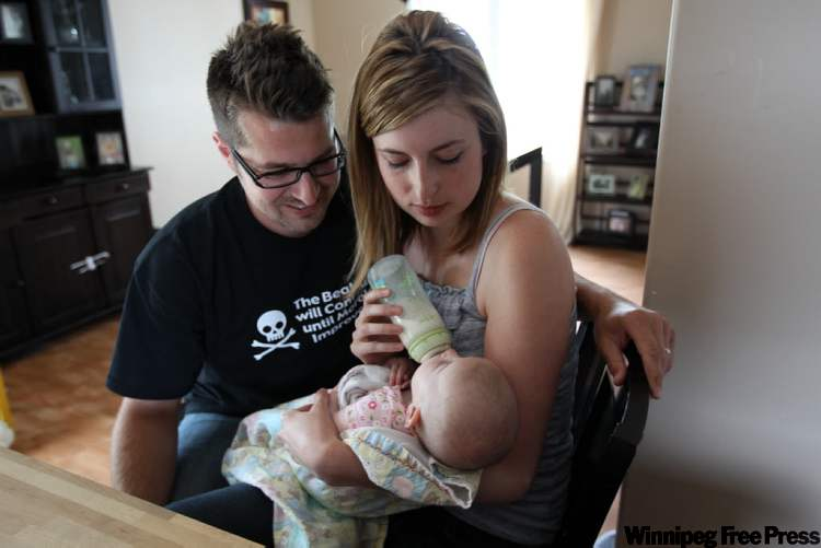 David Weber and his wife Genevieve admire four-month-old Anabela who was born shortly after a harrowing journey to the hospital and two speeding tickets.