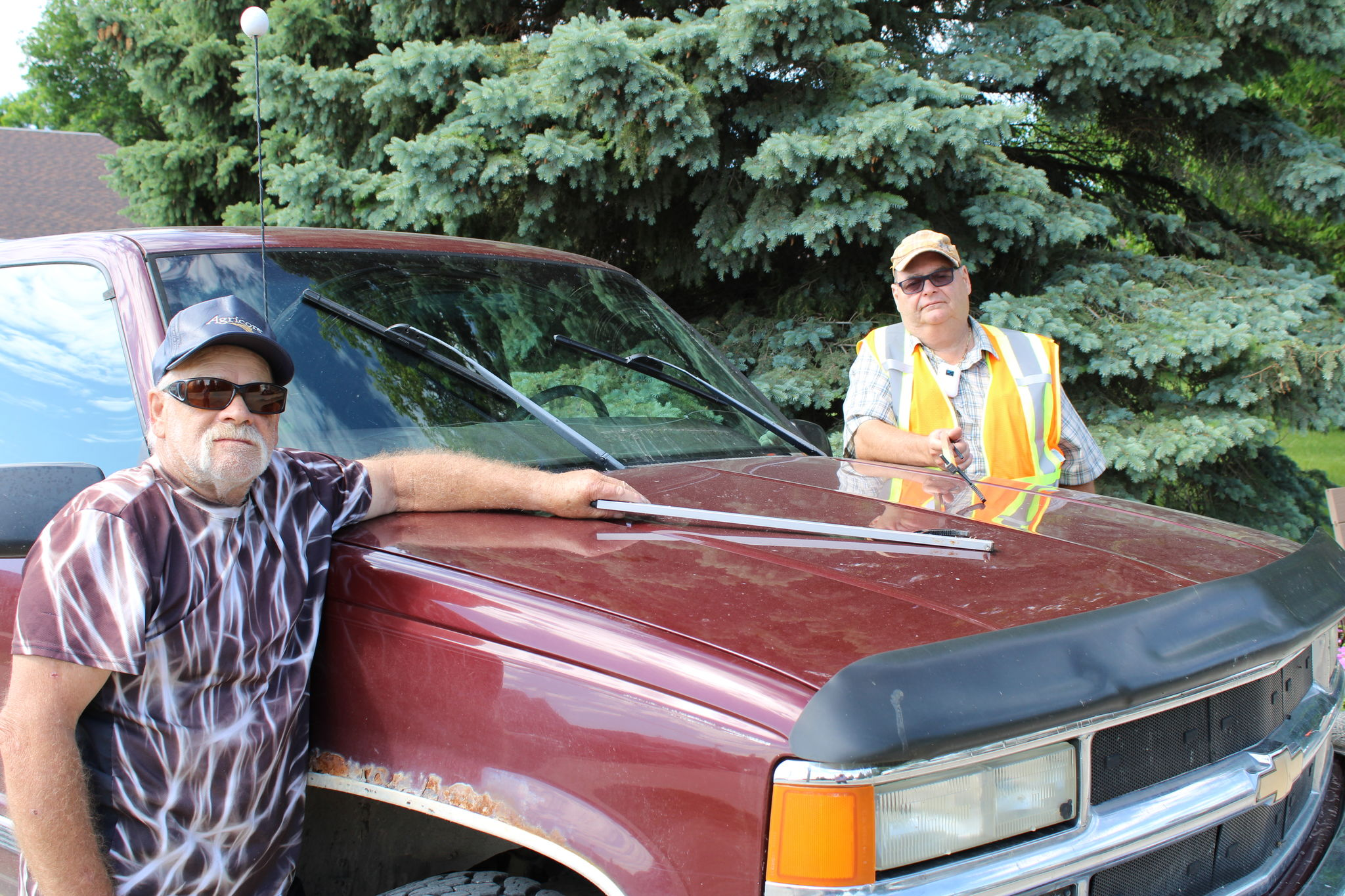 Abe Krause and Cecil Bayliss with the truck they use to canvas the countryside in search of garbage.