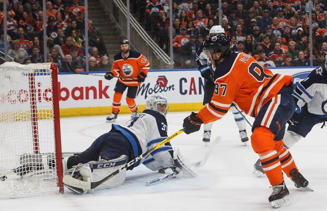 Winnipeg Jets goalie Connor Hellebuyck (37) is scored on by Edmonton Oilers' Connor McDavid (97) during second period NHL action in Edmonton, Alta., on Wednesday March 11, 2020.The NHL says it is evaluating its options for the rest of the 2019-20 season after the NBA suspended its season until further notice on Wednesday night. THE CANADIAN PRESS/Jason Franson