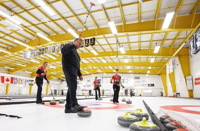 Coach Marcel Rocque raises his broom as, from left, Emma Miskew, Lisa Weagle, and Joanne Courtney, practice in Leduc, Alta., on Friday September 7, 2018. THE CANADIAN PRESS/Jason Franson